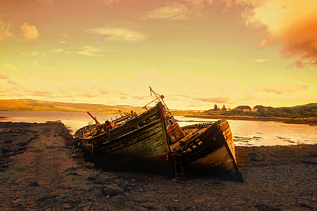 two brown boats dock on beach sand during golden hour