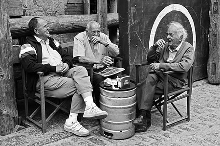 grayscale photography of three men sitting on chair while talking to each other