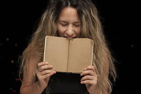 woman biting a brown book
