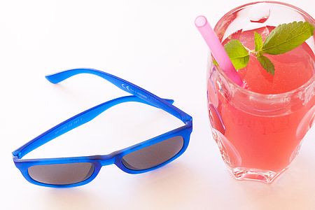 blue framed Wayfarer-style sunglasses near glass cup with juice drink