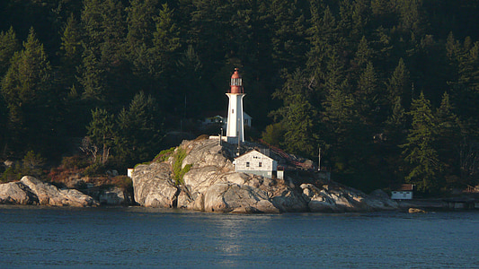 white and orange lighthouse near body of water