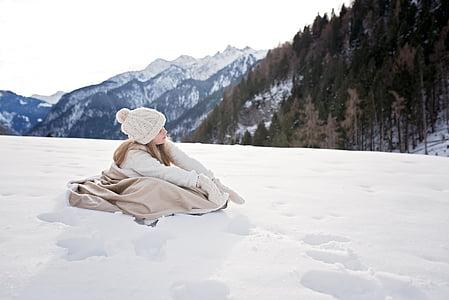 girl wearing winter coat sitting on snow field