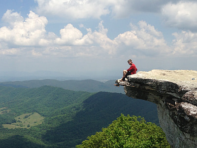 man sitting on ledge of rock
