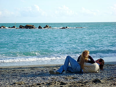 couple laying on beach side photography