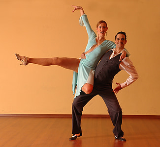 man lifting his dance partner inside well lighted room