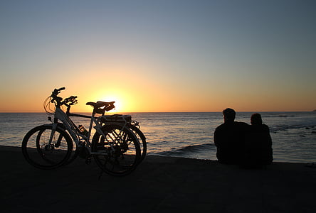 silhouette photography of two person sitting beach shore beside bicycles
