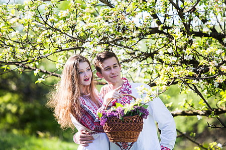 man and woman gathering flowers