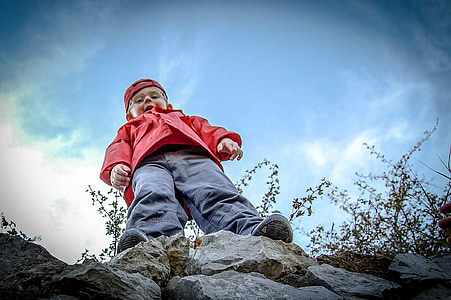 boy wearing gray pants standing on rock boulder