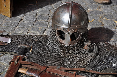 gray chain mail helmet and armor on gray brick floor