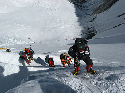 group of people hiking on snow mountain cliff
