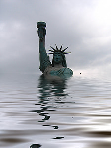 male raising torch statue surrounded by body of water