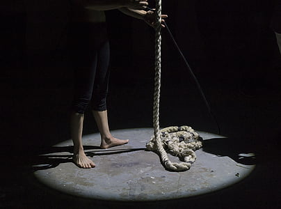 person standing on floor holding brown rope
