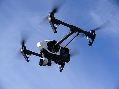 black and white quadcopter drone under cloudy blue sky