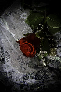 red rose beside silver-colored rosary on white lace textile