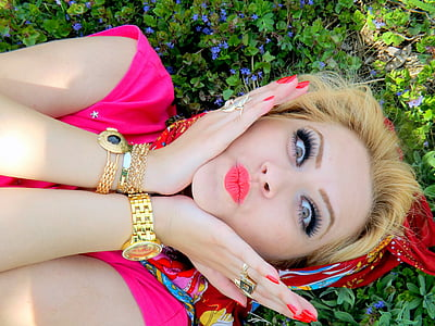 closeup photo of a girl lying on a bed of flower her hands on her cheeks