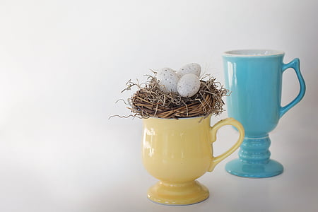 yellow and teal ceramic footed mugs with three eggs