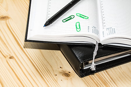 black ballpoint pen beside three green clips on white book page