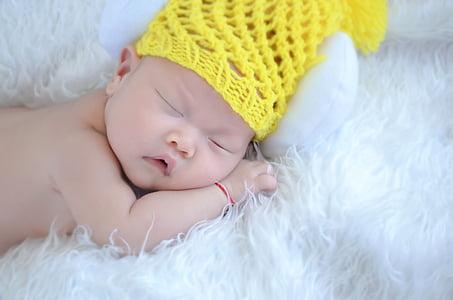 sleeping baby wearing yellow knit cap laying on white fleece textile