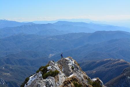 man on top of rock mountain during daytime