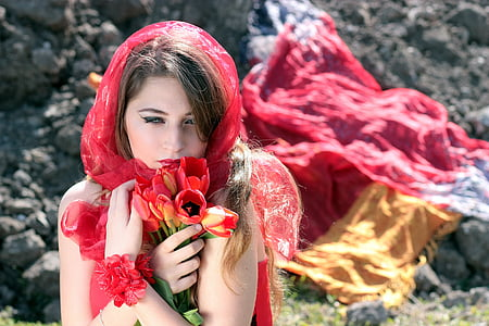 close-up photography of woman wearing red scarf and holding red and yellow tulip flowers