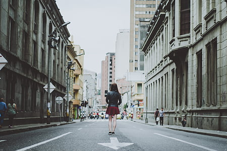 woman wearing red skirt standing in the middle of the city road