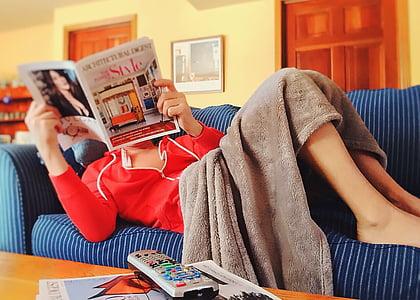 woman reading magazine lying on sofa