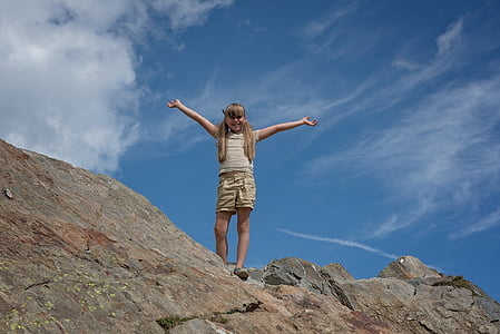 girl spread her arms on top of hill