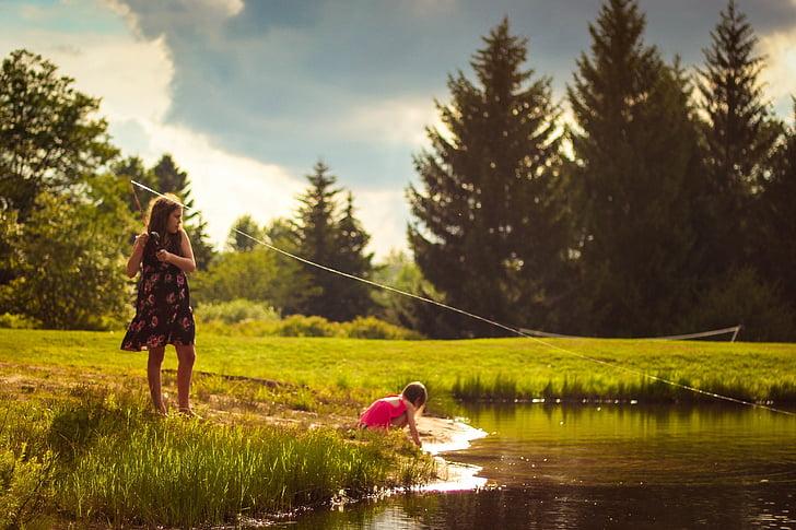 girl sitting near lake