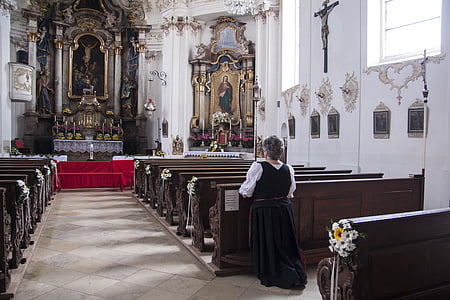 woman kneeling her nee on church while prayingh