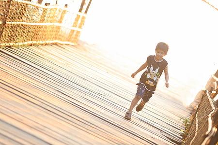 boy wearing black sonic printed tank top running on brown wooden bridge