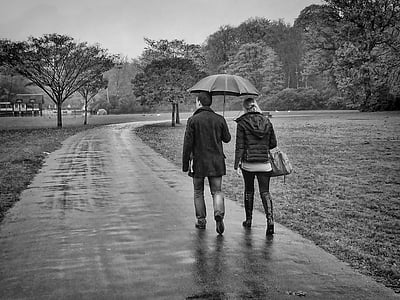 grayscale photo of couple walking on pavement while raining
