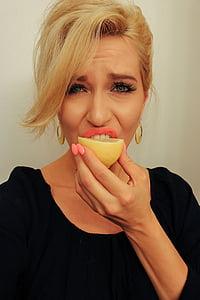 woman biting lemon