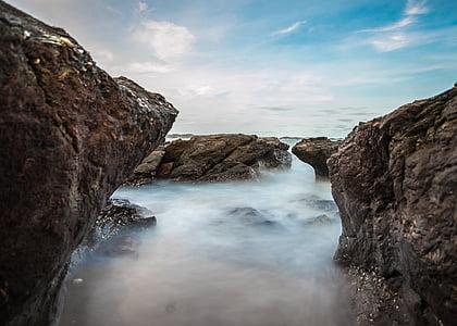 waterfalls between rock boulders