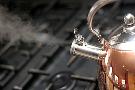 steam coming out of whistling kettle on stove