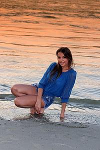 woman sitting on beach shore