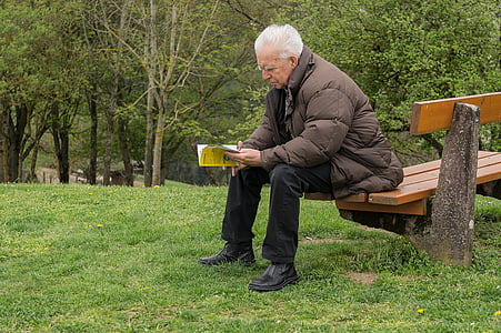 man sitting on the bench reading book