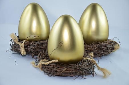 three gold decorative eggs