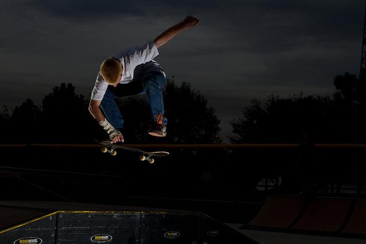man in white shirt skateboarding during night