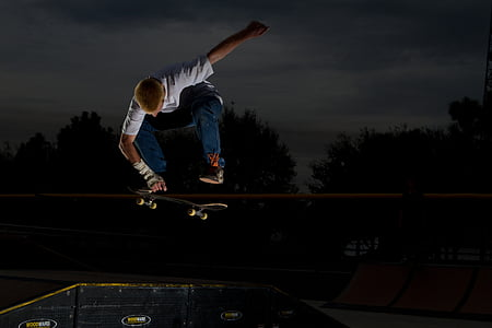 man in white shirt skateboarding during night