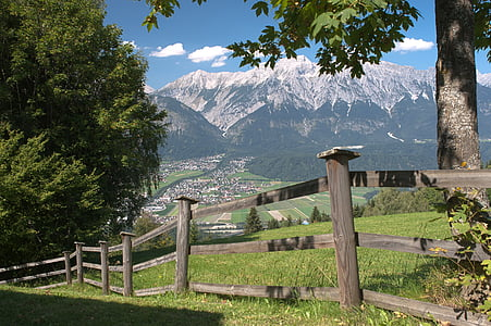 brown wooden fence near trees and mountain near town
