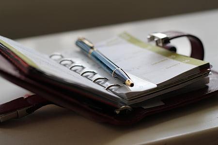 photo of blue ballpoint pen on notebook