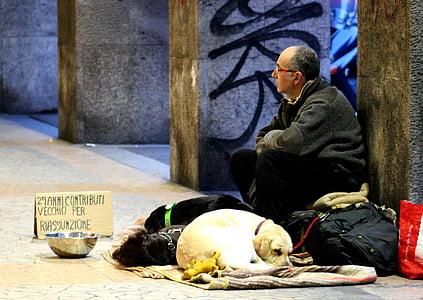 man wearing gray jacket sitting beside short-coated white dog