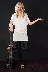 woman holding black bass electric guitar