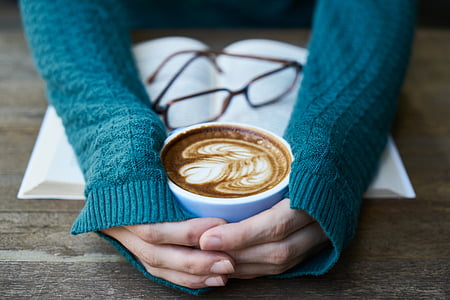 person's hand holding white ceramic coffee mug filled with latte