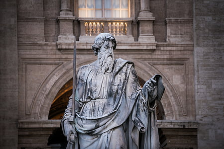 closeup photo of man holding bar statue