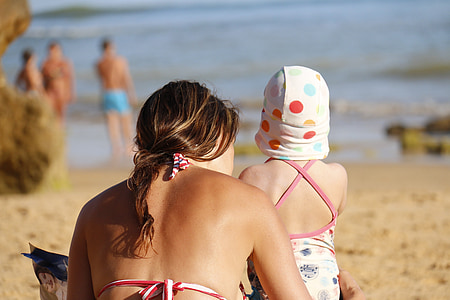 woman and baby sitting beside beach