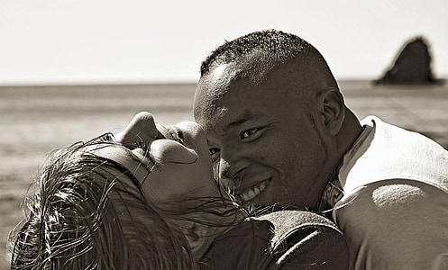smiling man looking on woman in grayscale photography