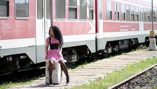 woman wearing pink and white polka-dot dress beside train