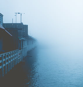elevated houses beside body of water in foggy weather condition