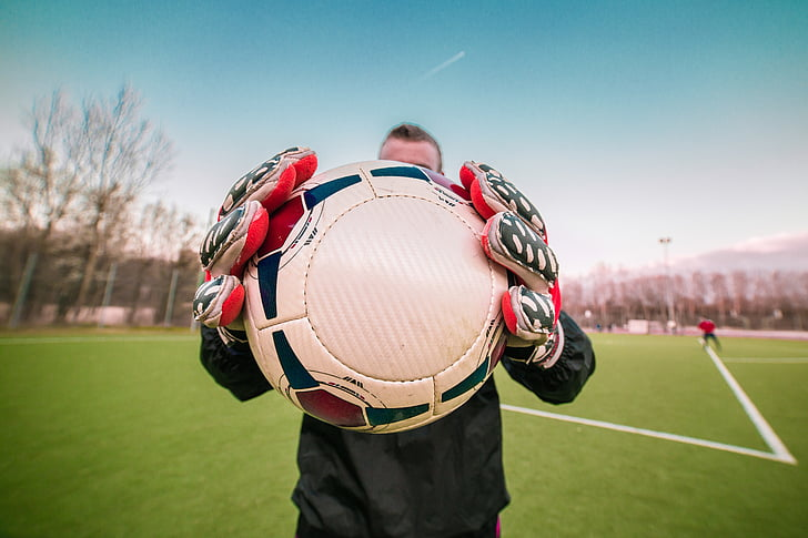 soccer player holding white and black ball